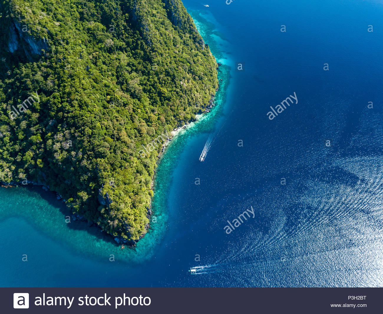 Aerial drone view down onto boats over a tropical coral reef surrounded by mountains and jungle - Stock Image