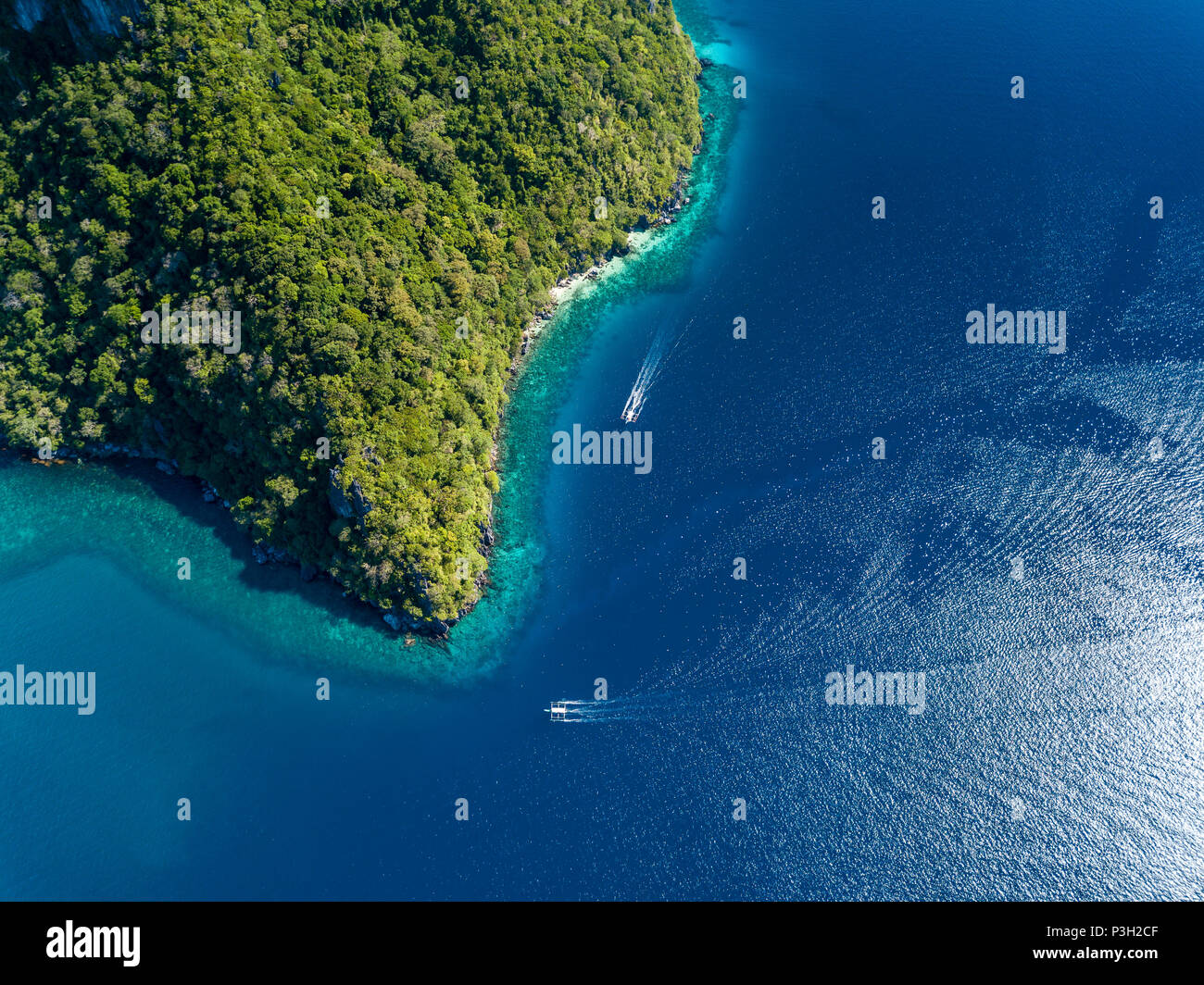 Aerial drone view down onto boats over a tropical coral reef surrounded by mountains and jungle Stock Photo