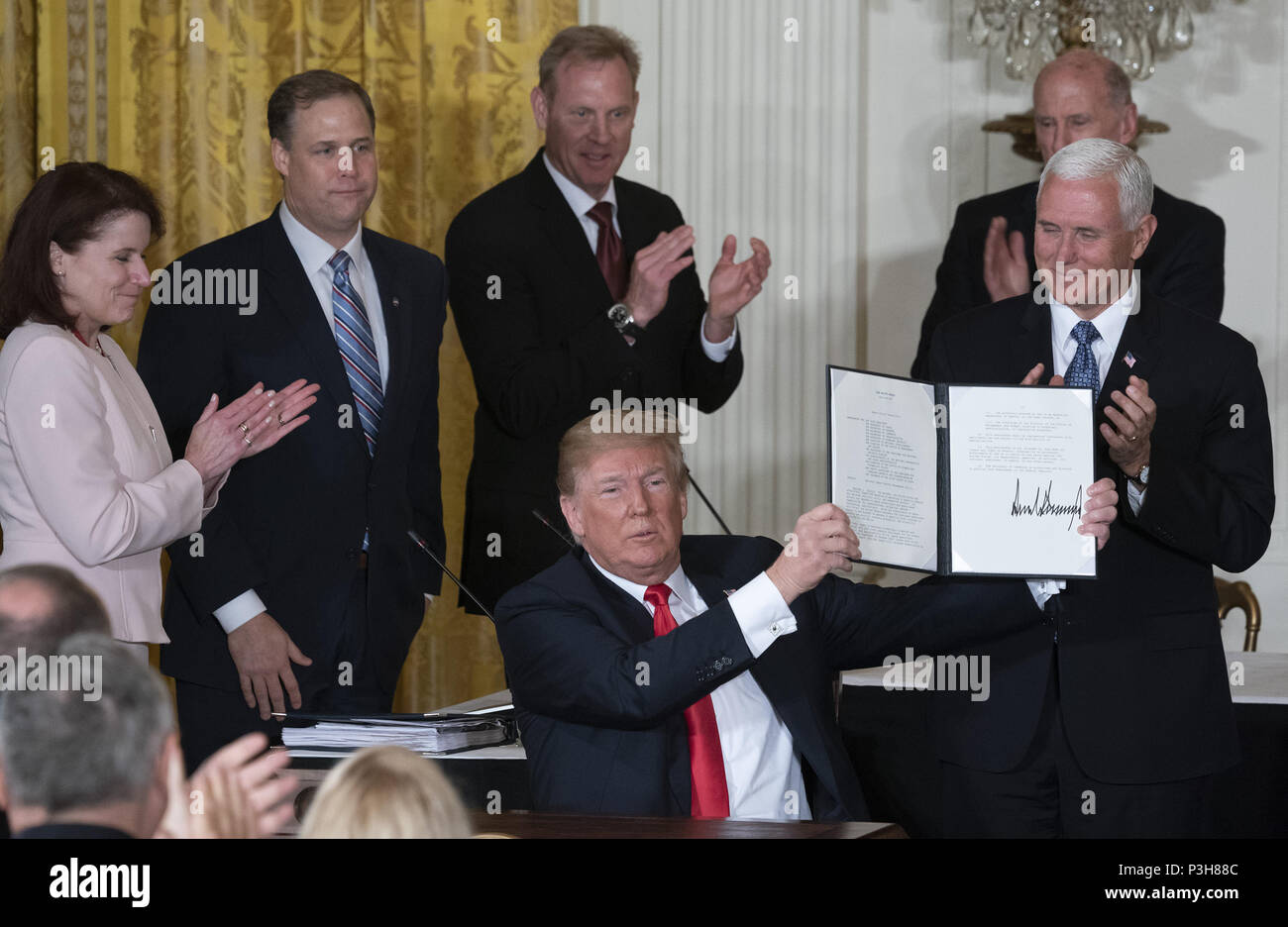 Washington, District of Columbia, USA. 18th June, 2018. United States President Donald J. Trump displays Space Policy Directive 3, signed during a meeting of the National Space Council at The White House in Washington, DC, June 18, 2018. The directive addresses issues including monitoring of objects in orbit, providing that information to spacecraft operators to avoid collisions, and to limit the growth of orbital debris. Chris Kleponis/CNP Credit: Chris Kleponis/CNP/ZUMA Wire/Alamy Live News - Stock Image