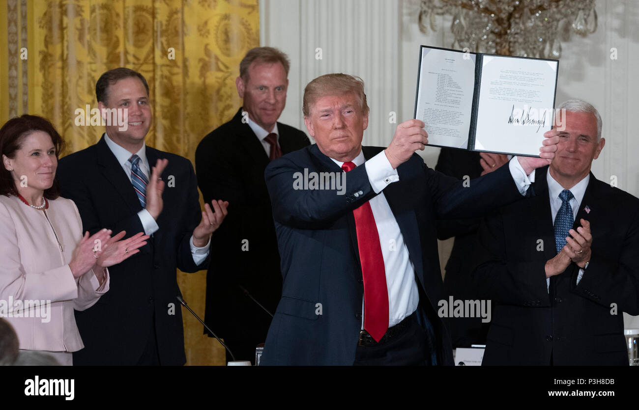 United States President Donald J. Trump displays Space Policy Directive 3, signed during a meeting of the National Space Council at The White House in Washington, DC, June 18, 2018. The directive addresses issues including monitoring of objects in orbit, providing that information to spacecraft operators to avoid collisions, and to limit the growth of orbital debris. Chris Kleponis/CNP | usage worldwide - Stock Image