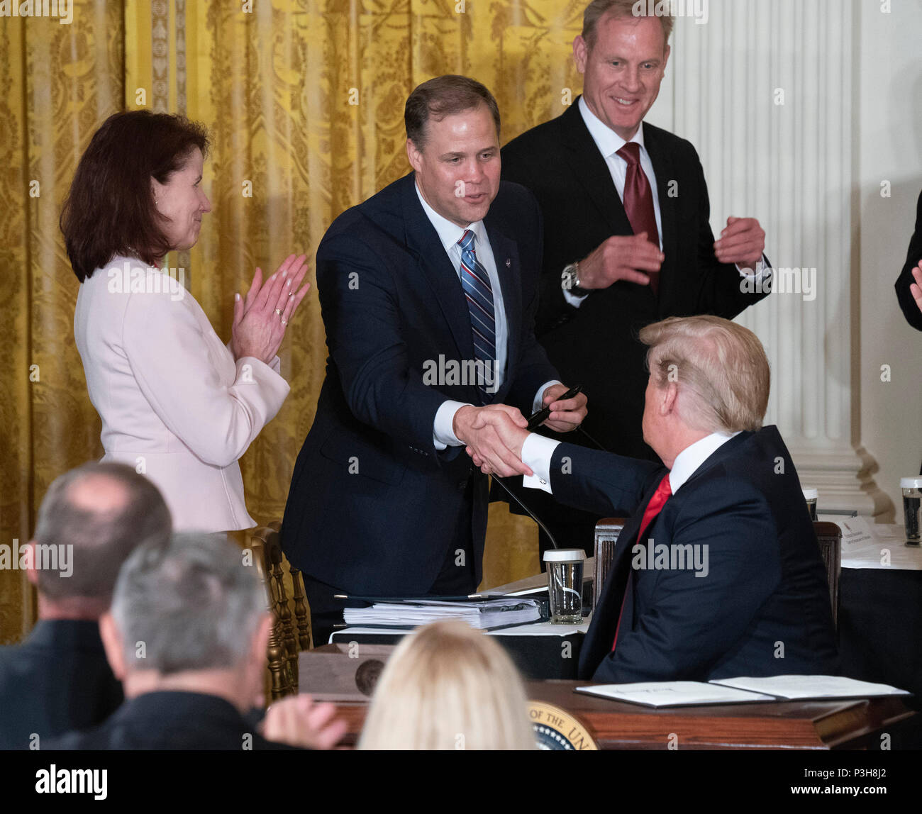 United States President Donald J. Trump hands off the pen used to sign Space Policy Directive 3 to Jim Bridenstine, administrator of the during a meeting with the National Space Council at The White House in Washington, DC, June 18, 2018. The directive addresses issues including monitoring of objects in orbit, providing that information to spacecraft operators to avoid collisions, and to limit the growth of orbital debris. Chris Kleponis/CNP /MediaPunch - Stock Image