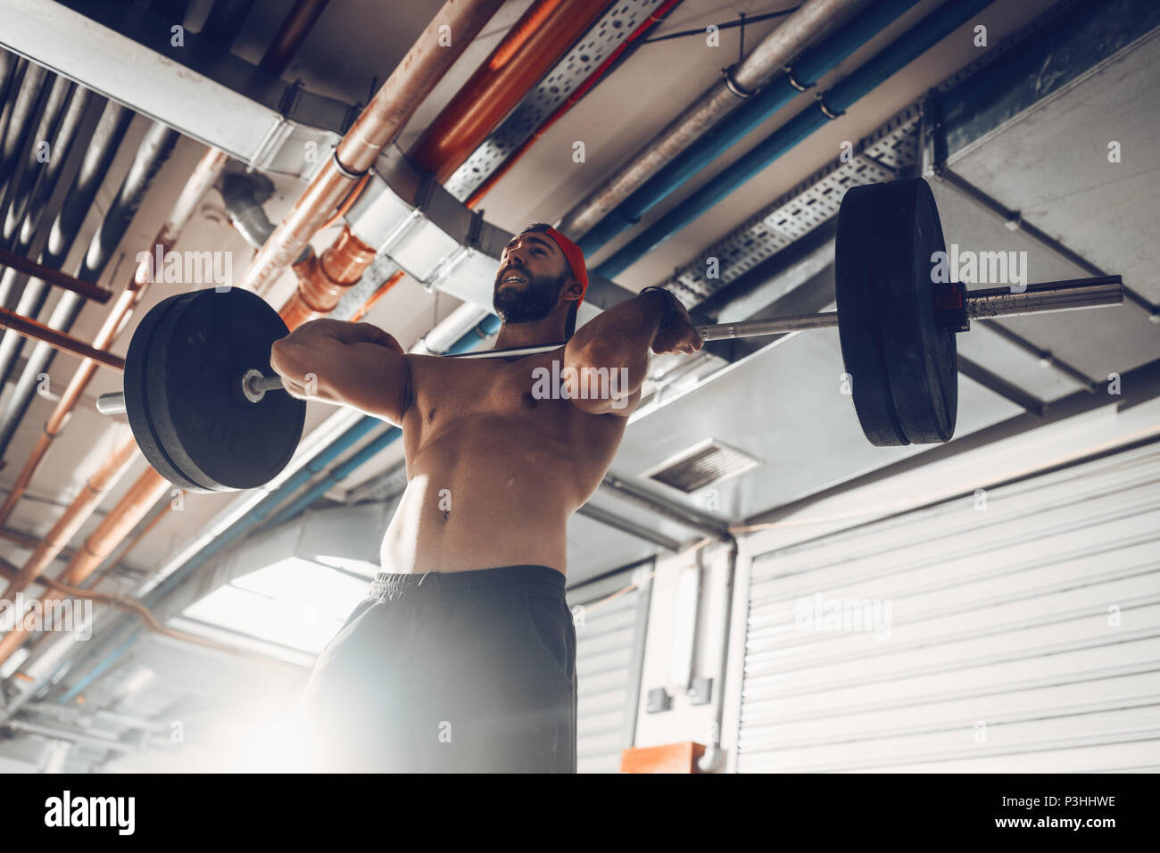 Young muscular man doing power clean exercise with barbell on hard