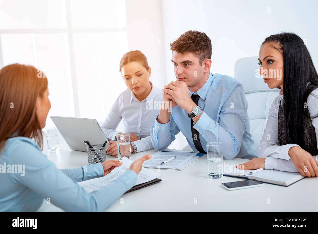 Young businesswoman in front of the commission having a job interview. - Stock Image