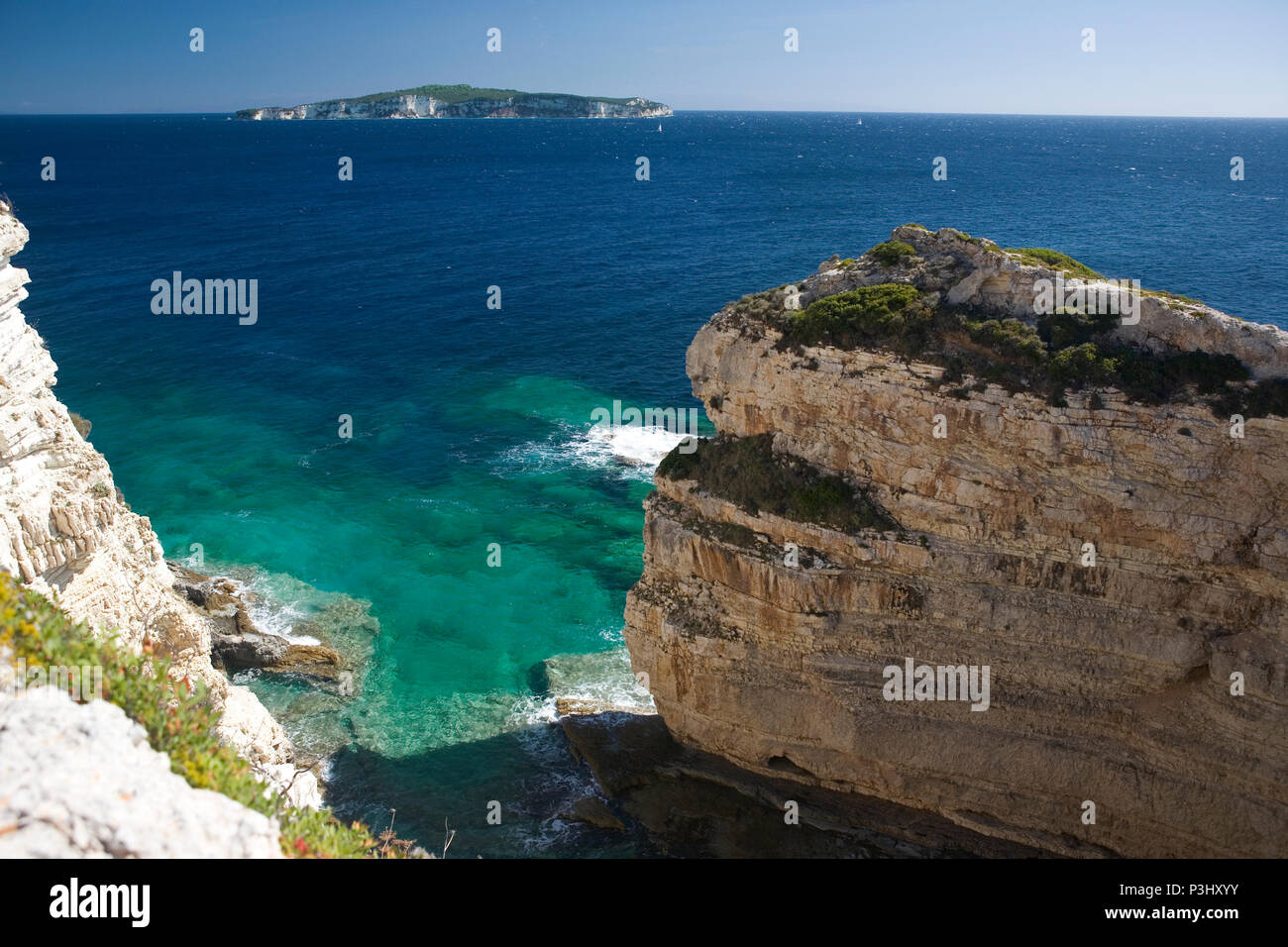 Looking south from the southern end of Paxos by Tripitos Arch to the island of Antipaxos, Greece - Stock Image