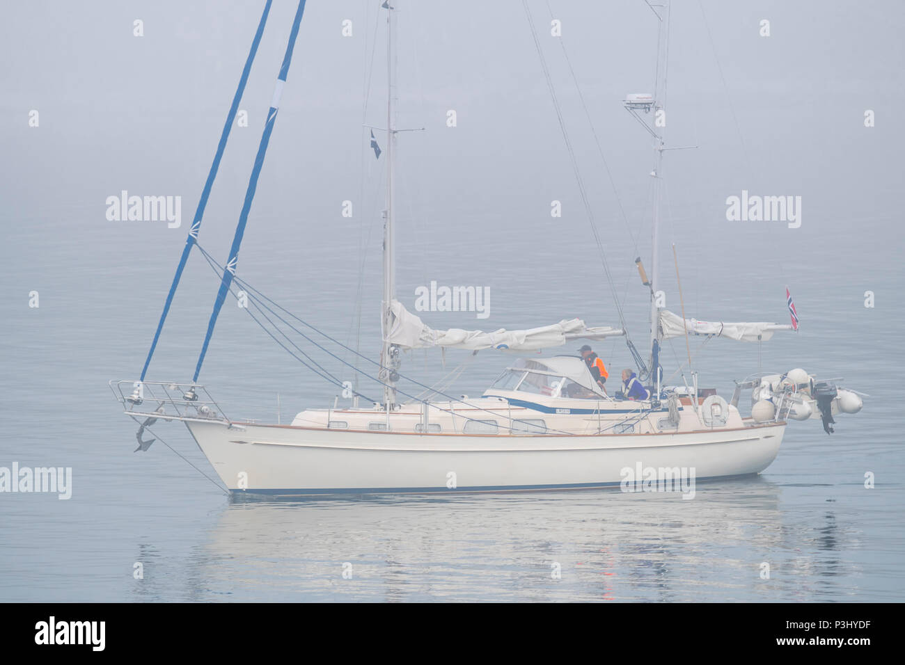 Sailboat / sailing boat / yacht with lowered sails at sea during bad visibility due to thick fog / dense mist - Stock Image