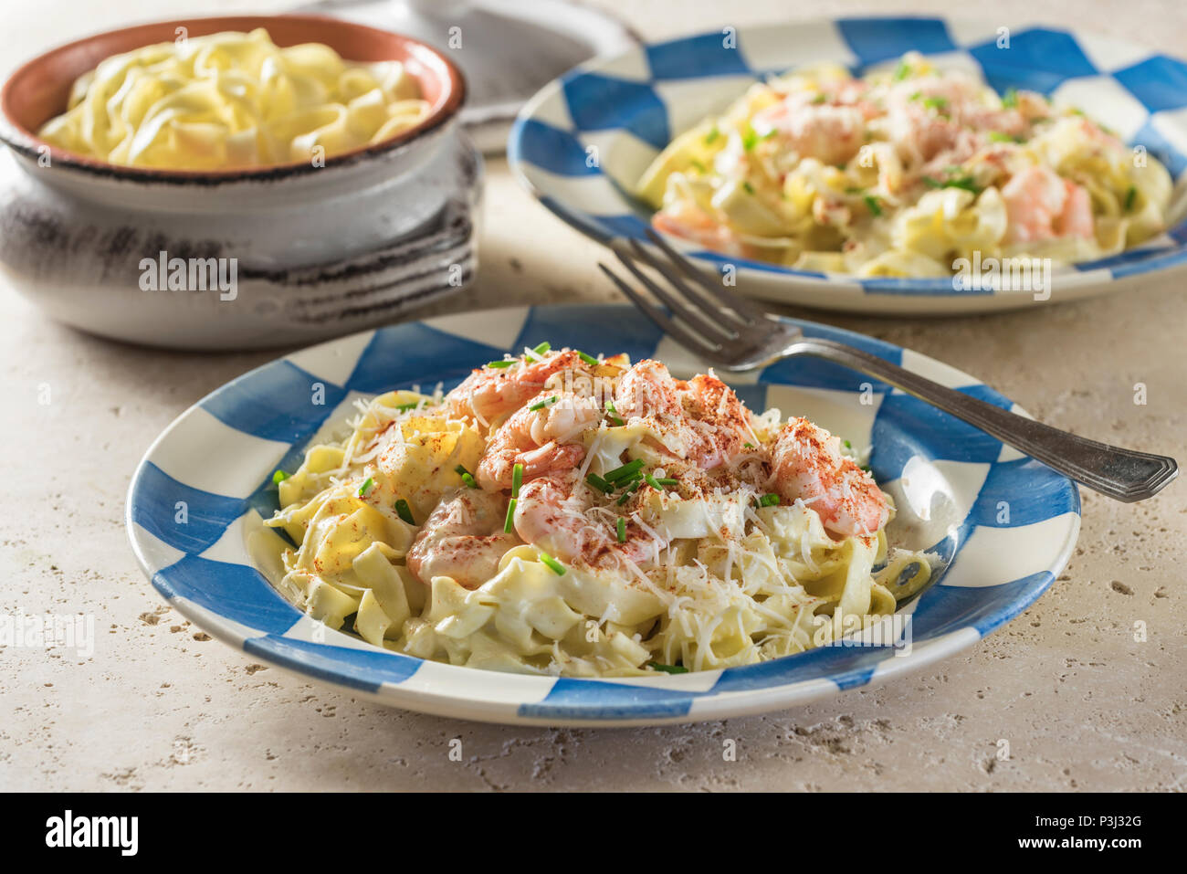 Shrimp Fettuccine Alfredo. Pasta in cheese and butter sauce with prawns. - Stock Image
