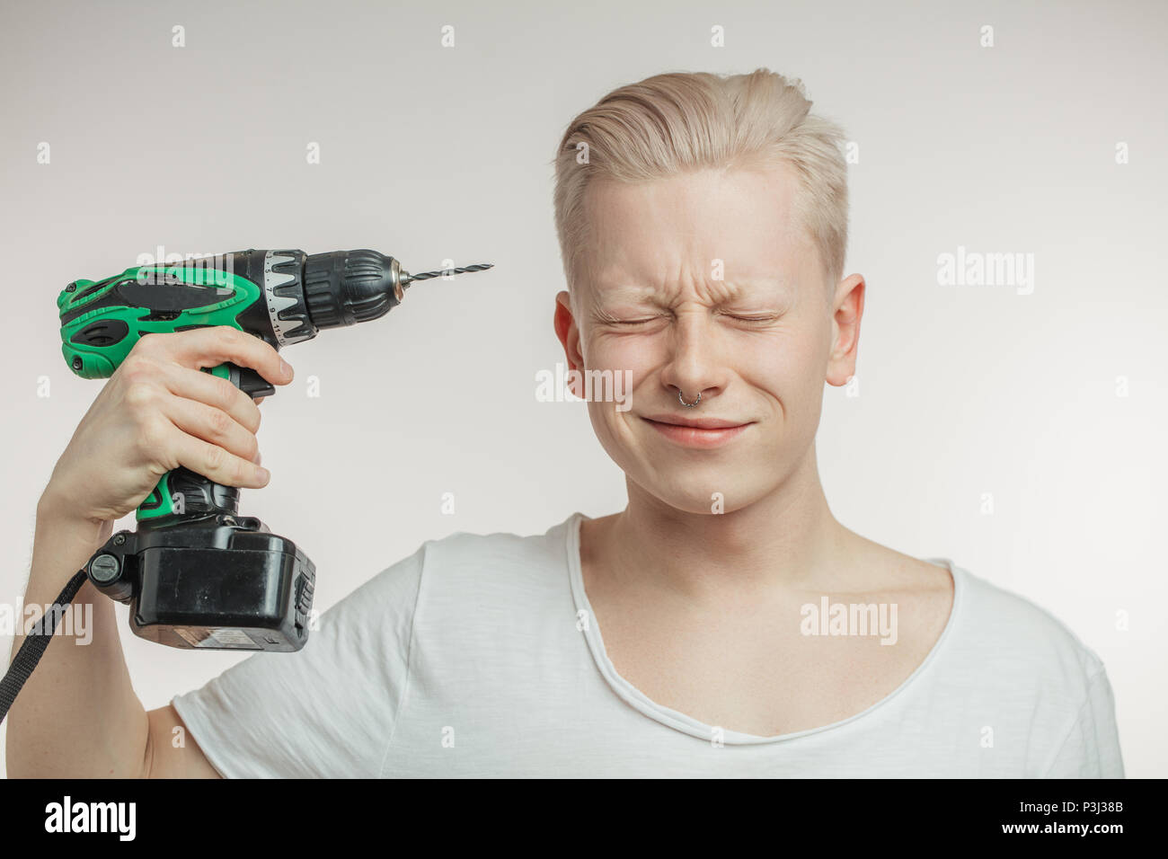 Man drilling a temple. Migraine, headache and masochism concept. Studio shot. - Stock Image
