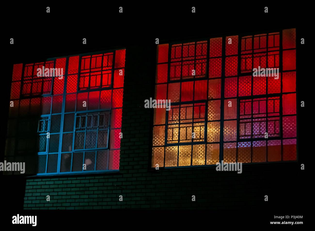 Red purple blue black light behind industrial steel window frames of ...