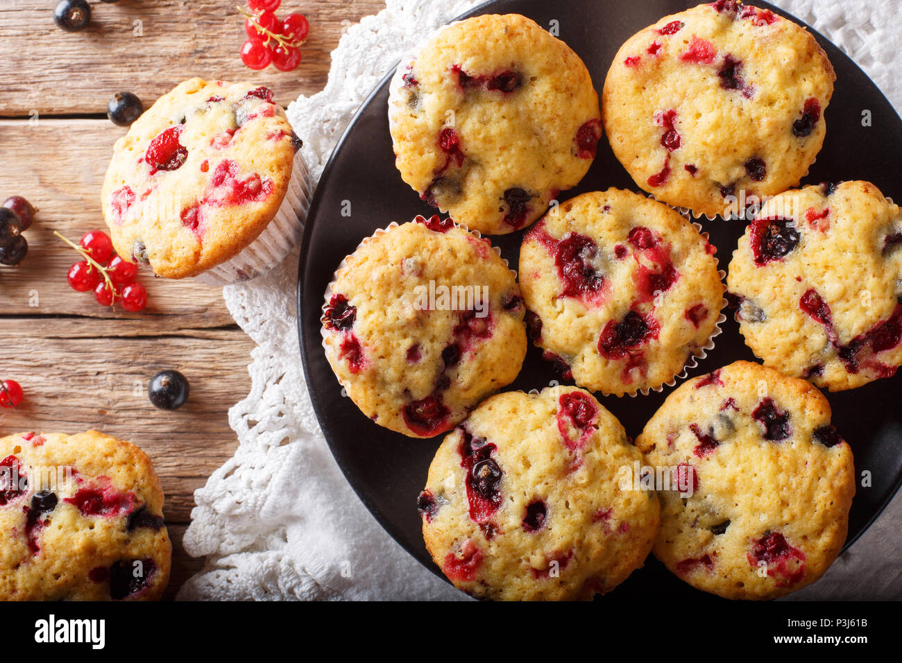 berry muffin with black and red currant close-up on the table. horizontal top view from above Stock Photo