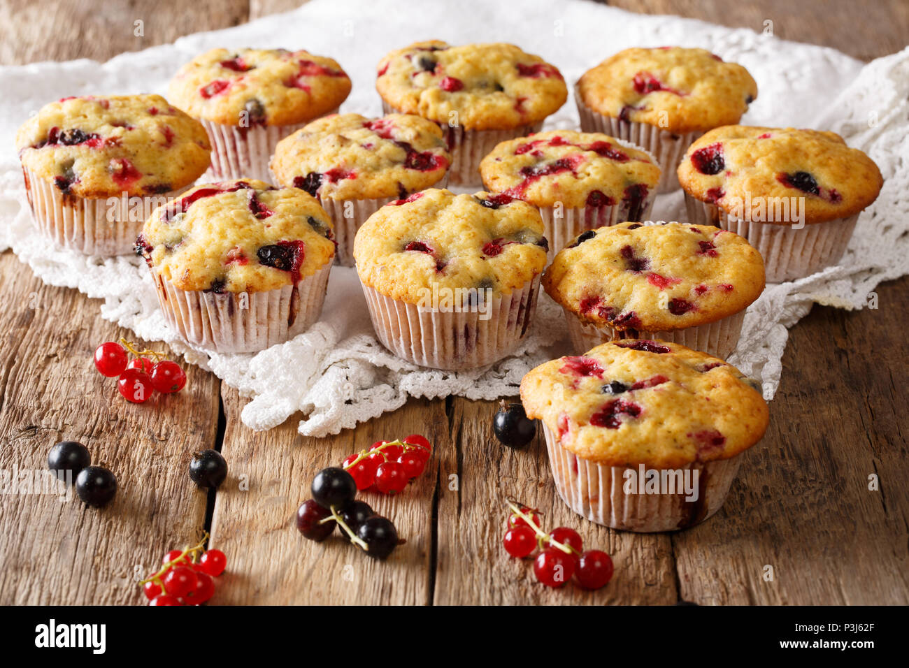 Freshly baked muffins with black and red currant berries close-up on the table. horizontal Stock Photo