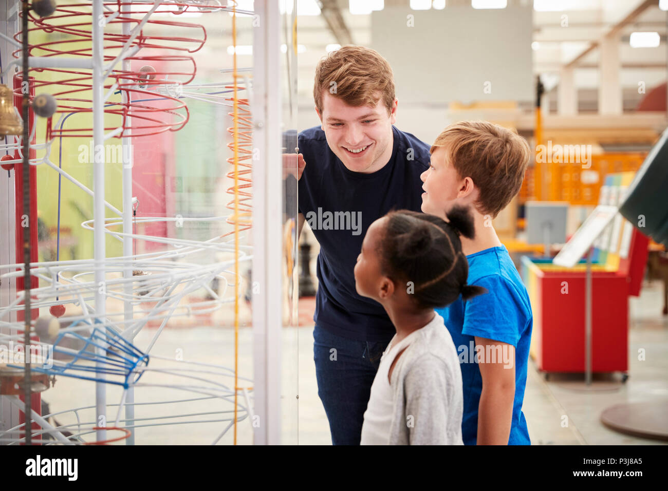 Teacher and kids talking about a science exhibit - Stock Image