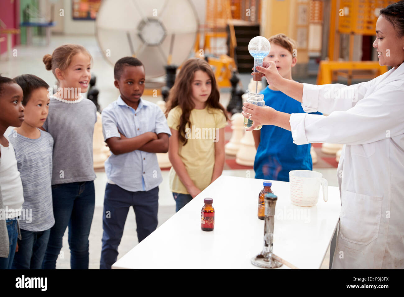 Kids watching lab technician carry out a science  experiment - Stock Image