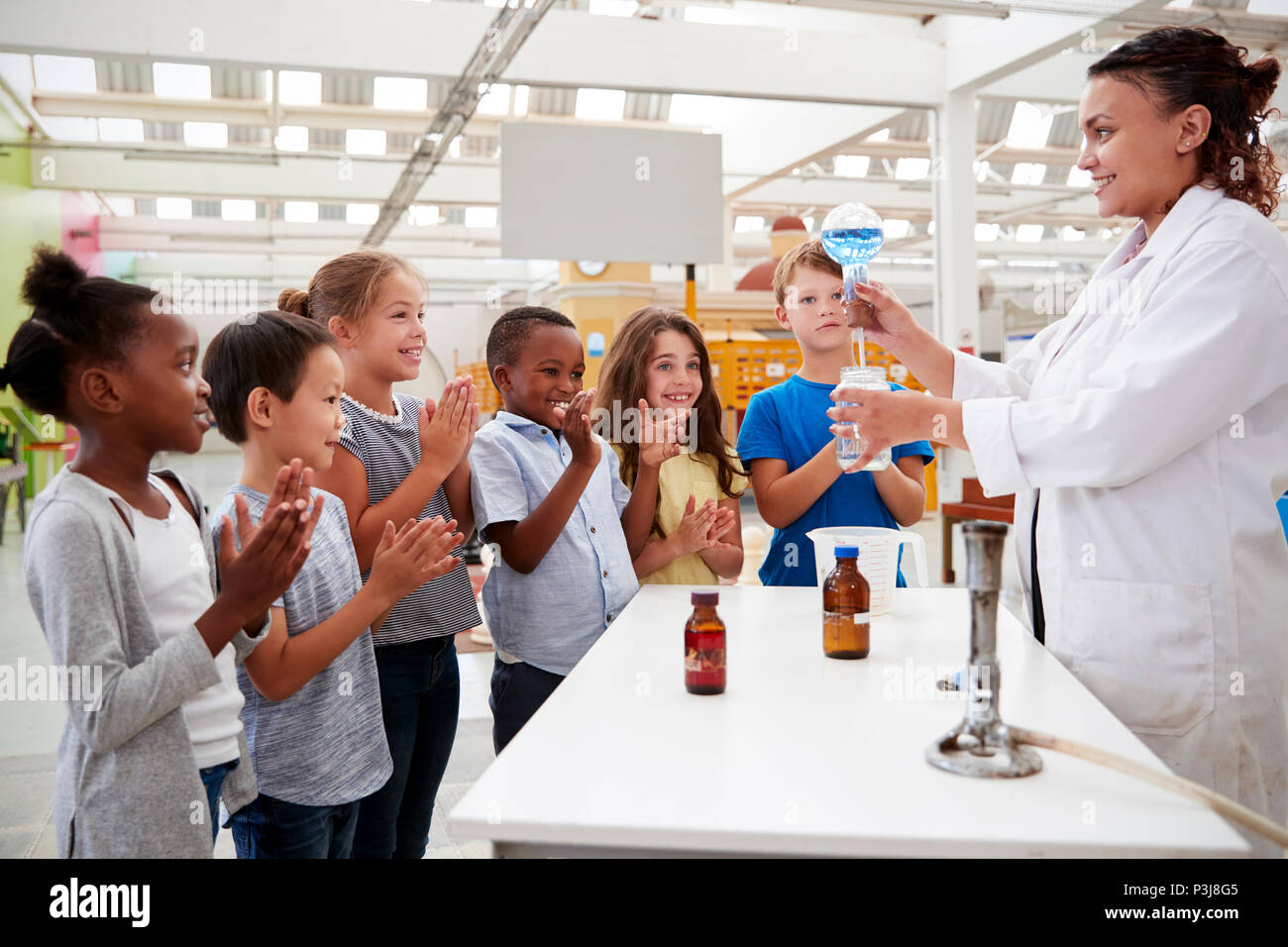 Lab technician showing excited kids a science experiment - Stock Image