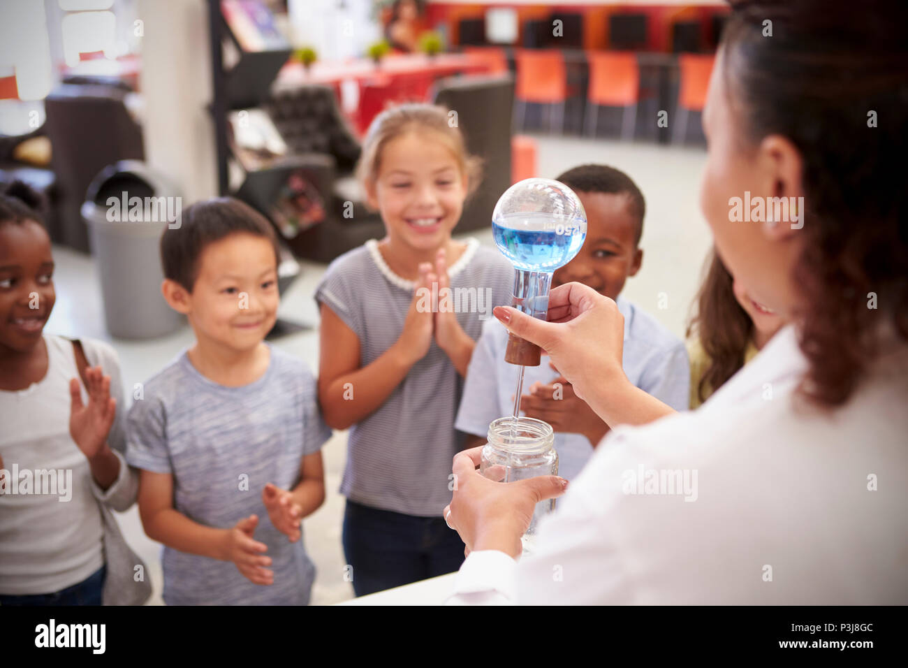 Lab technician showing excited kids an experiment, close up - Stock Image