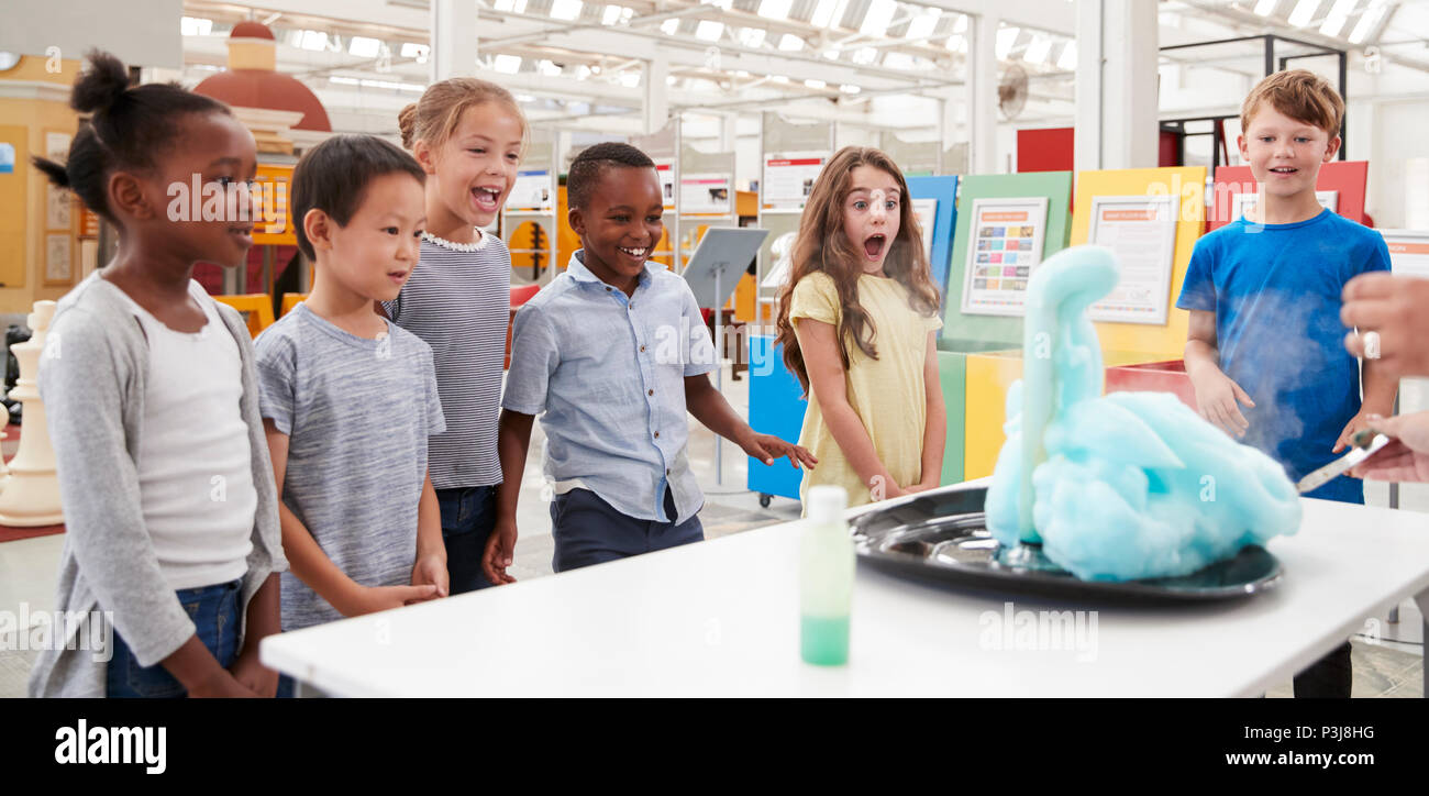 Kids having fun watching an experiment at a science centre - Stock Image