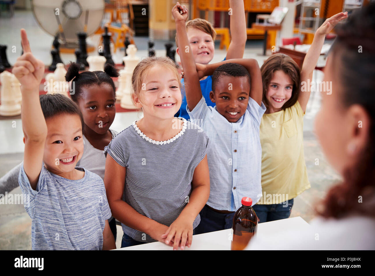 Group of kids volunteering to answer teacher's question - Stock Image