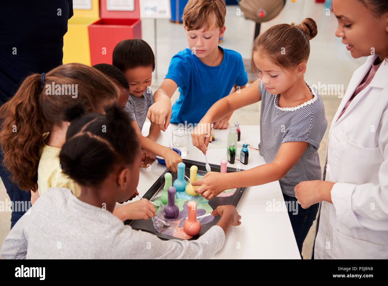 School kids taking part in experiment at science centre - Stock Image