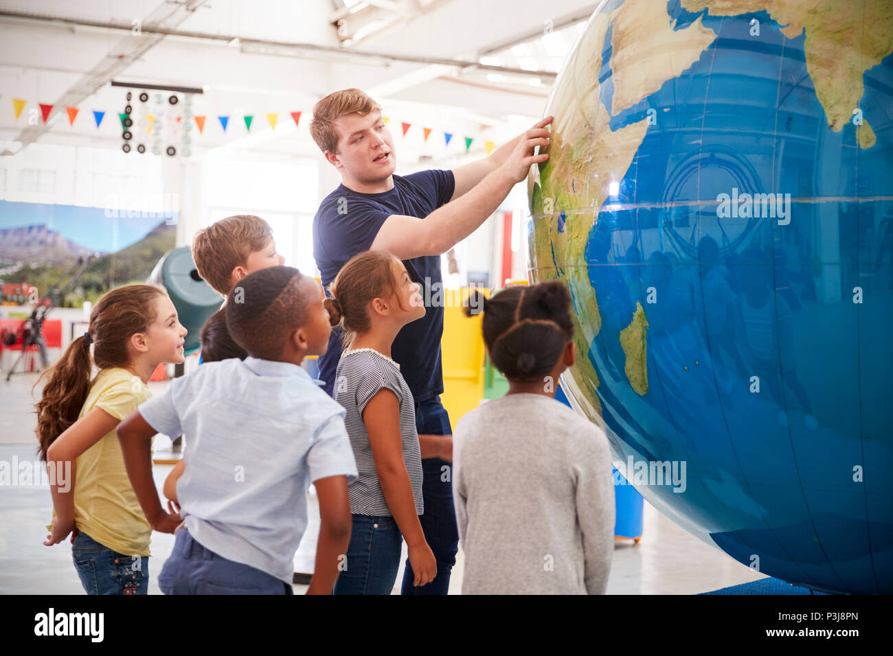 Kids watch presentation with giant globe at a science centre - Stock Image