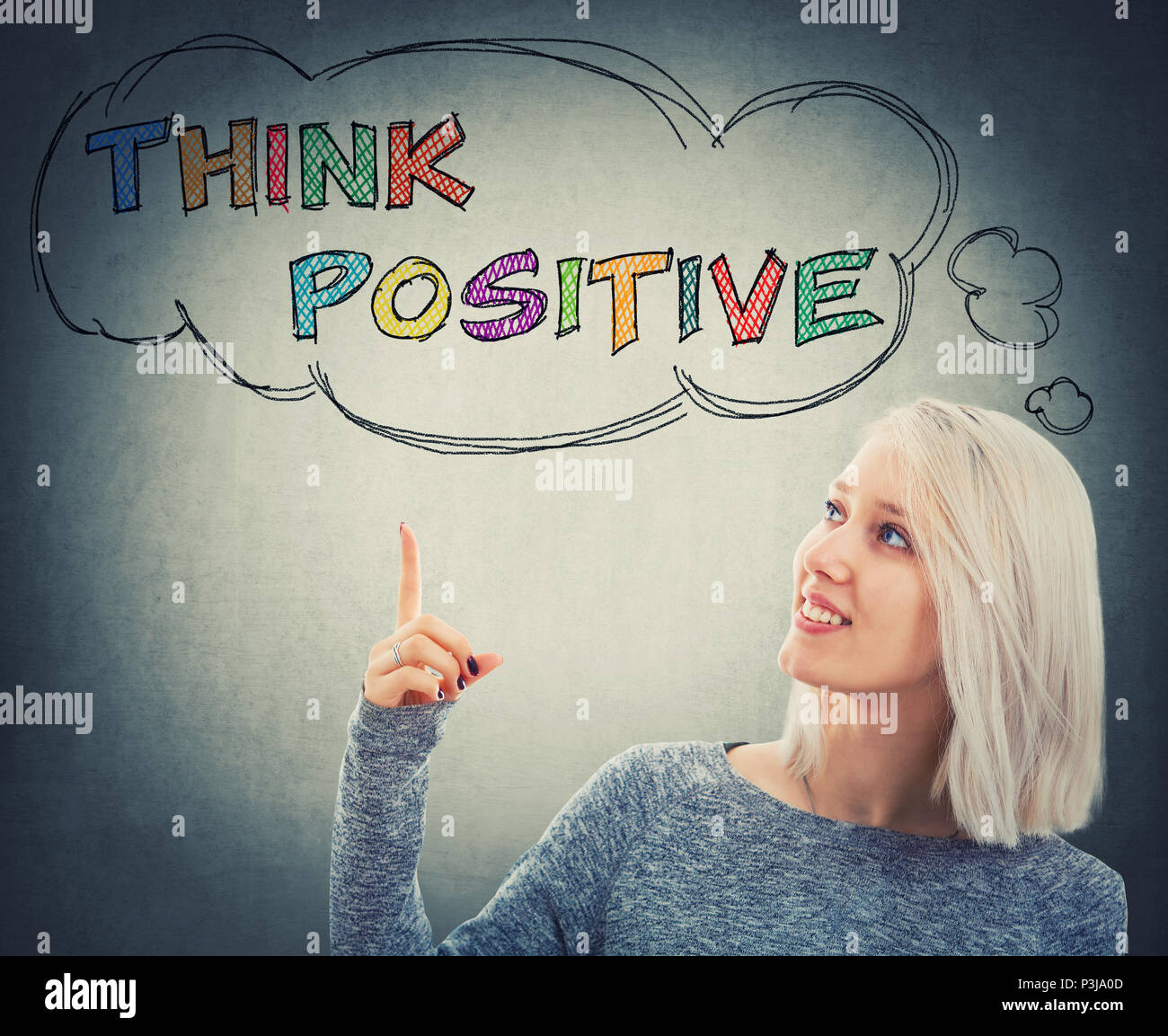 Portrait of smiling woman pointing her finger up to a thought bouble with the text think positive. Colorful motivatinal slogan, having fun, enjoy the  - Stock Image