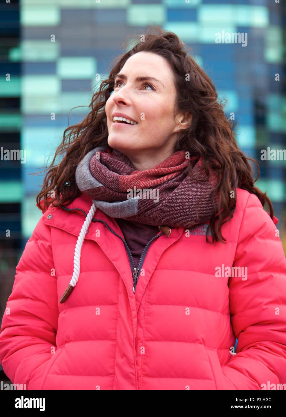 woman wearing big scarf smiling - Stock Image