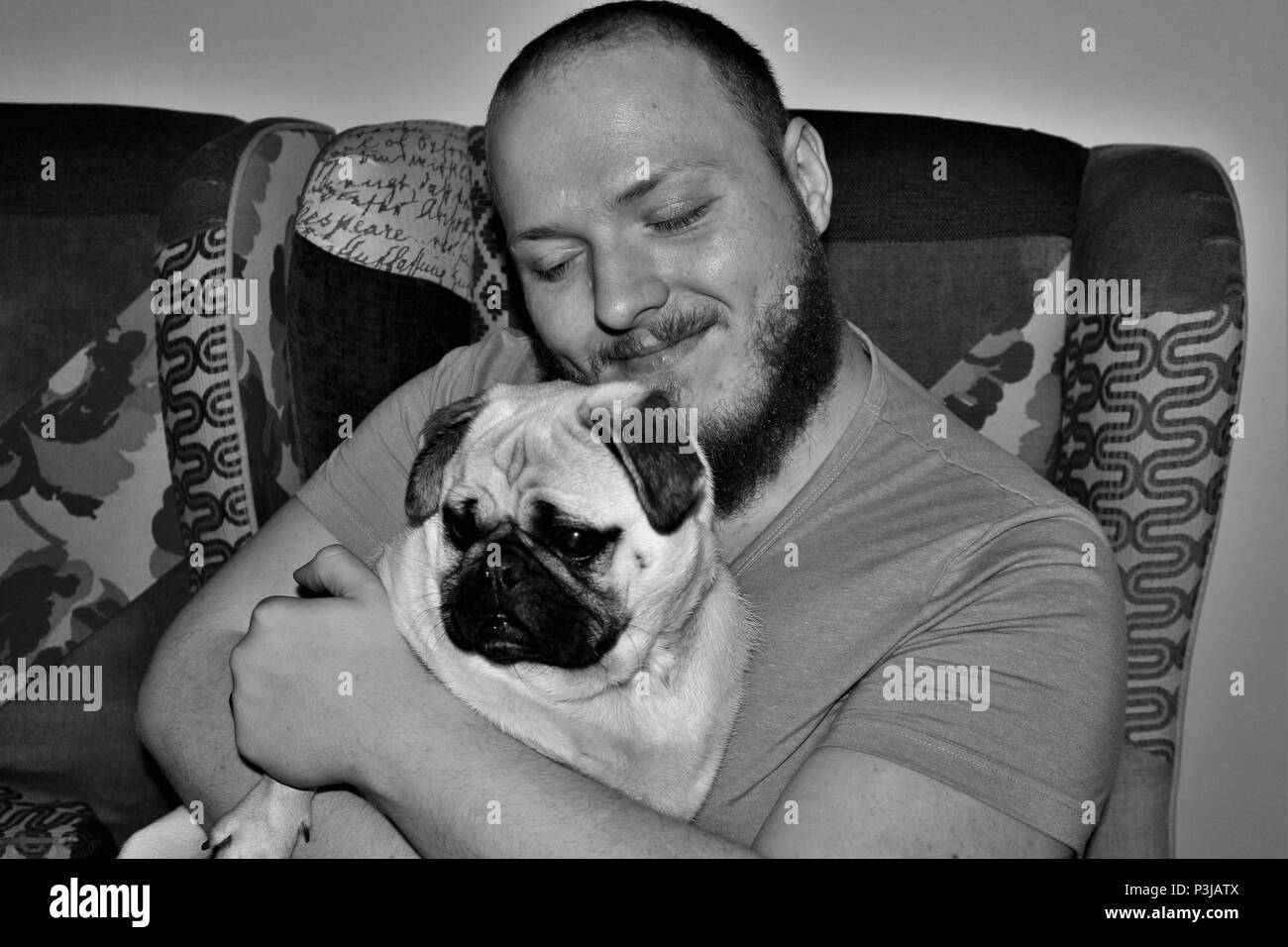 Caucasian man looking happy whilst cuddling his young Pug dog. - Stock Image