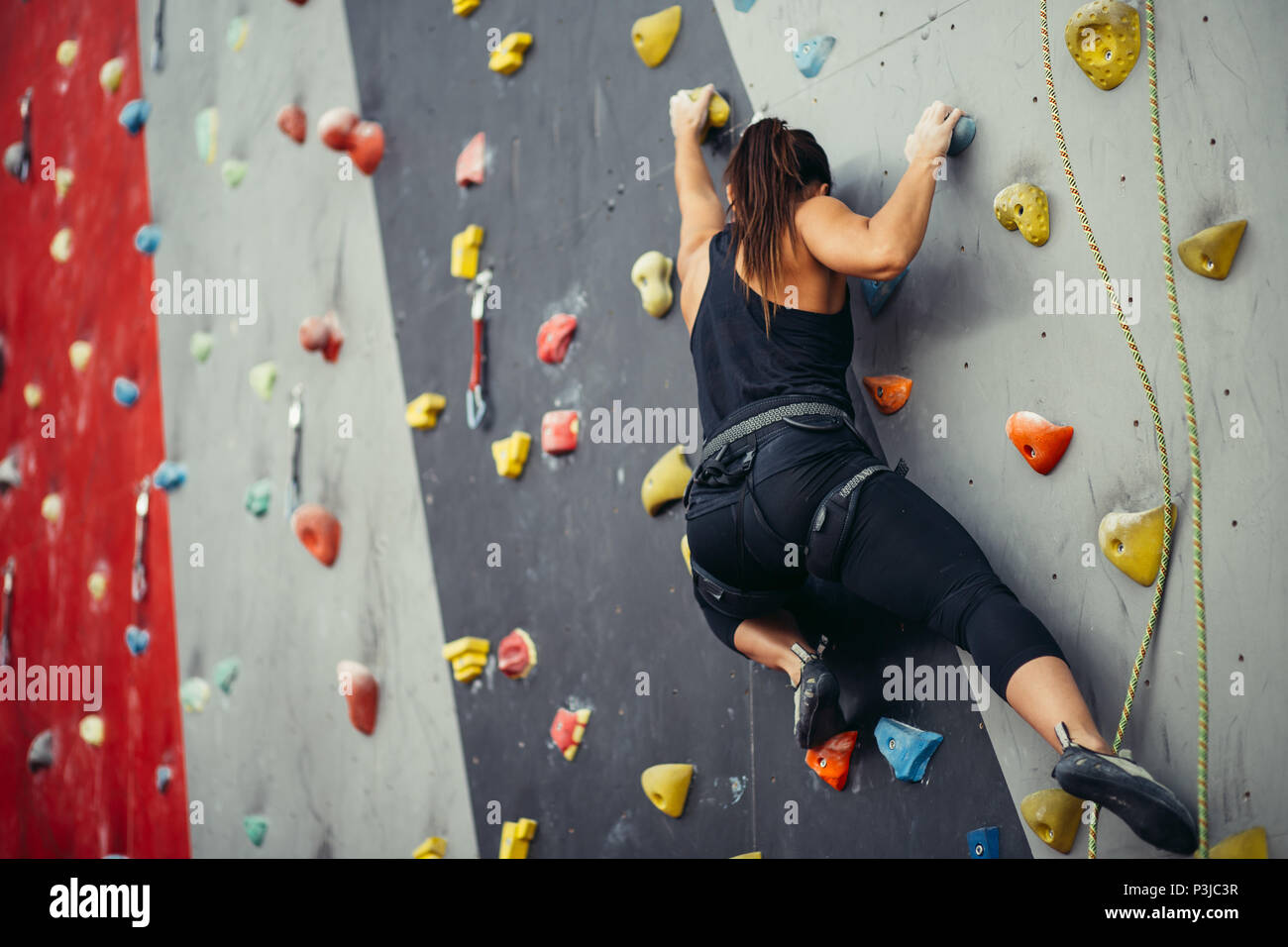 Sporty young woman training in a colorful climbing gym. - Stock Image