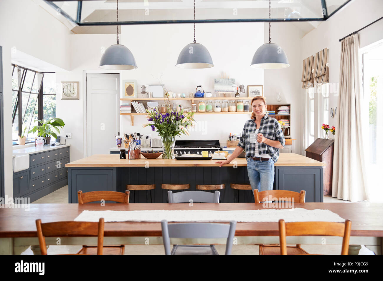 Woman Leaning On Island In An Open Plan Kitchen Dining Room