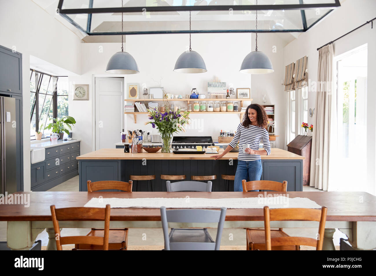 Mixed race woman leaning on kitchen island in open plan home & Mixed race woman leaning on kitchen island in open plan home Stock ...