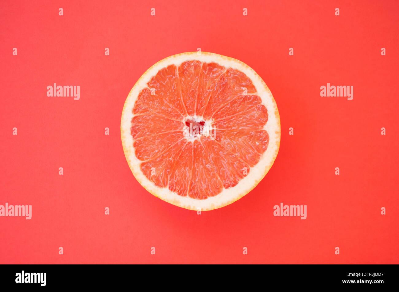 Beautiful juicy cut grapefruit on red background. Stock Photo