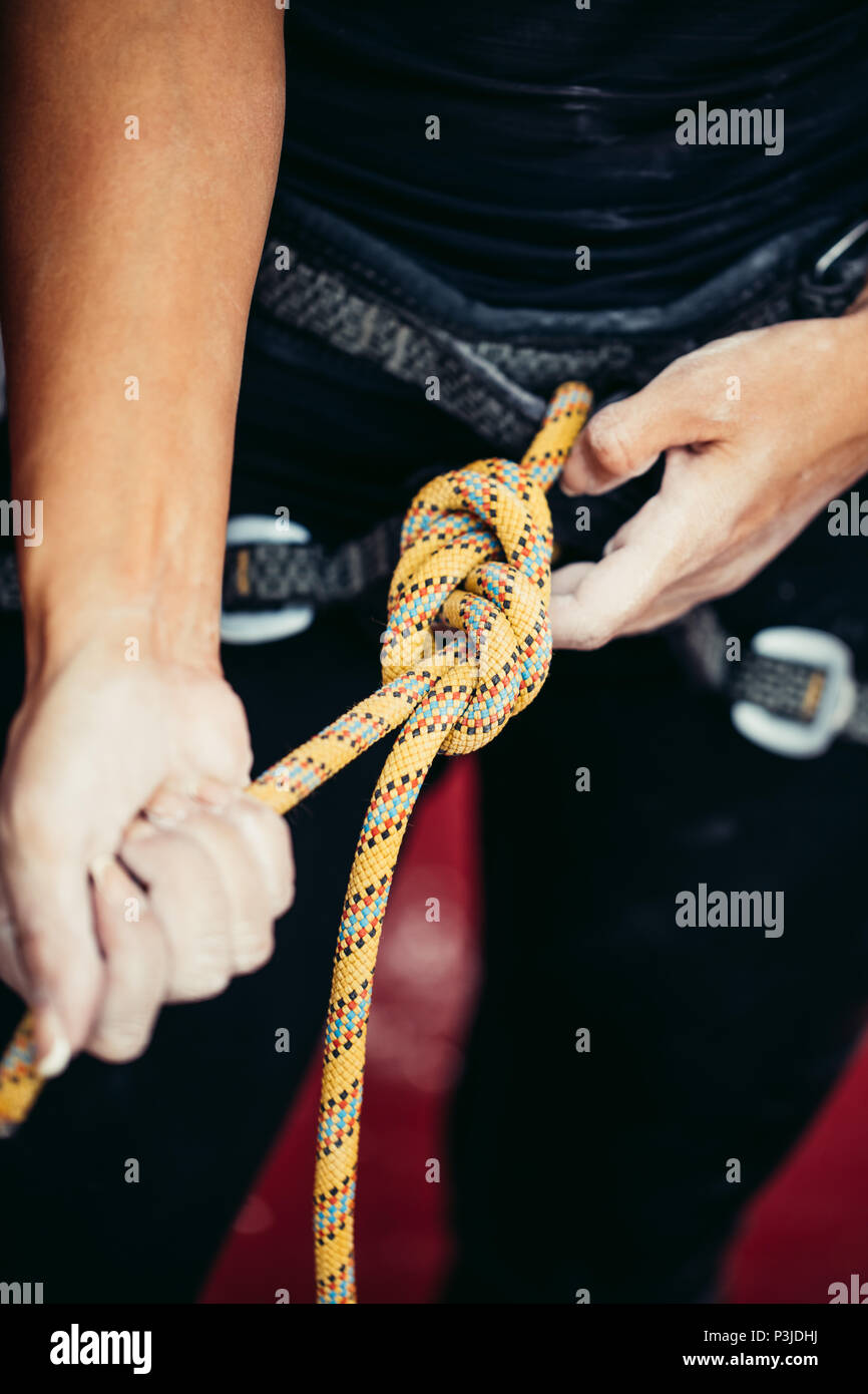 Rock climber wearing safety harness and safety rope in, close-up image - Stock Image