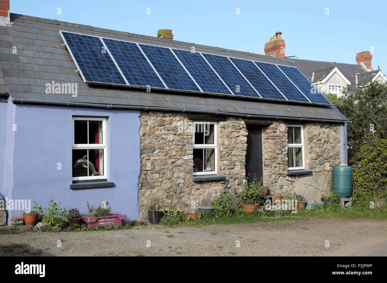 Photovoltaic cells solar panels on the roof of a small stone cottage in the village of Marloes Pembrokeshire Wales, UK  KATHY DEWITT - Stock Image