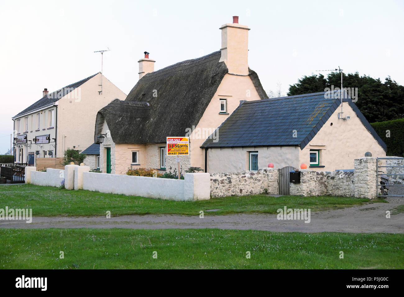 For sale sign on a thatched cottage in the village of Marloes Pembrokeshire Wales, UK  KATHY DE WITT Stock Photo