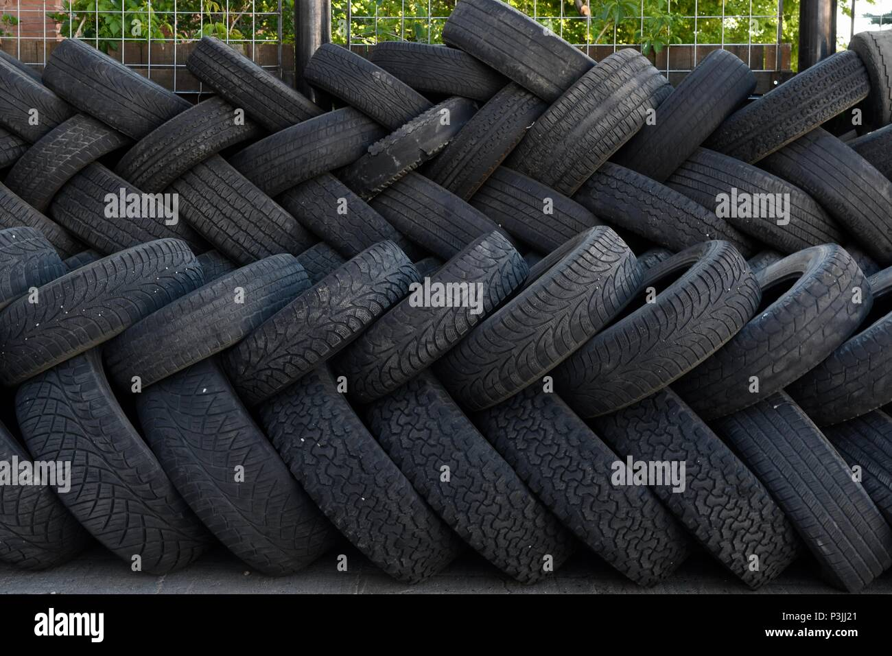 A gathering of tires in Salida Colorado, stacked in herringbone pattern - Stock Image