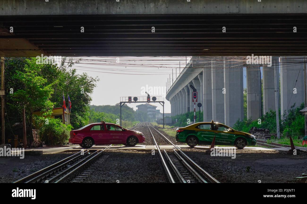 Bangkok, Thailand - Apr 20, 2018. Taxis running across railtracks at Lat Krabang Station in Bangkok, Thailand. - Stock Image