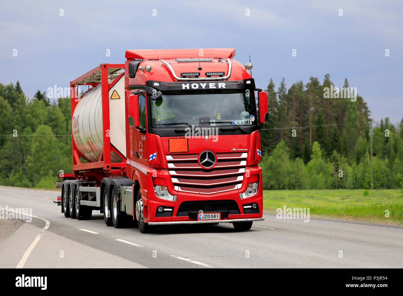 Red Mercedes-Benz 2551 truck of Hoyer Group transports tank container along  highway 4 in the summer. Uurainen, Finland - June 15, 2018.
