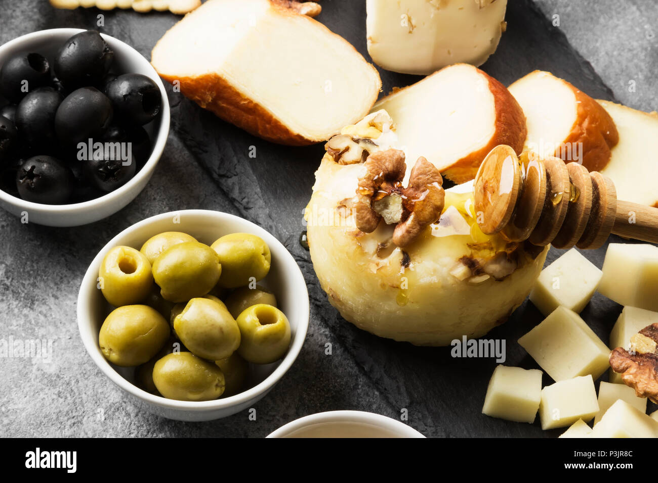 Snacks with wine - various types of cheeses, figs, nuts on a gray background Stock Photo