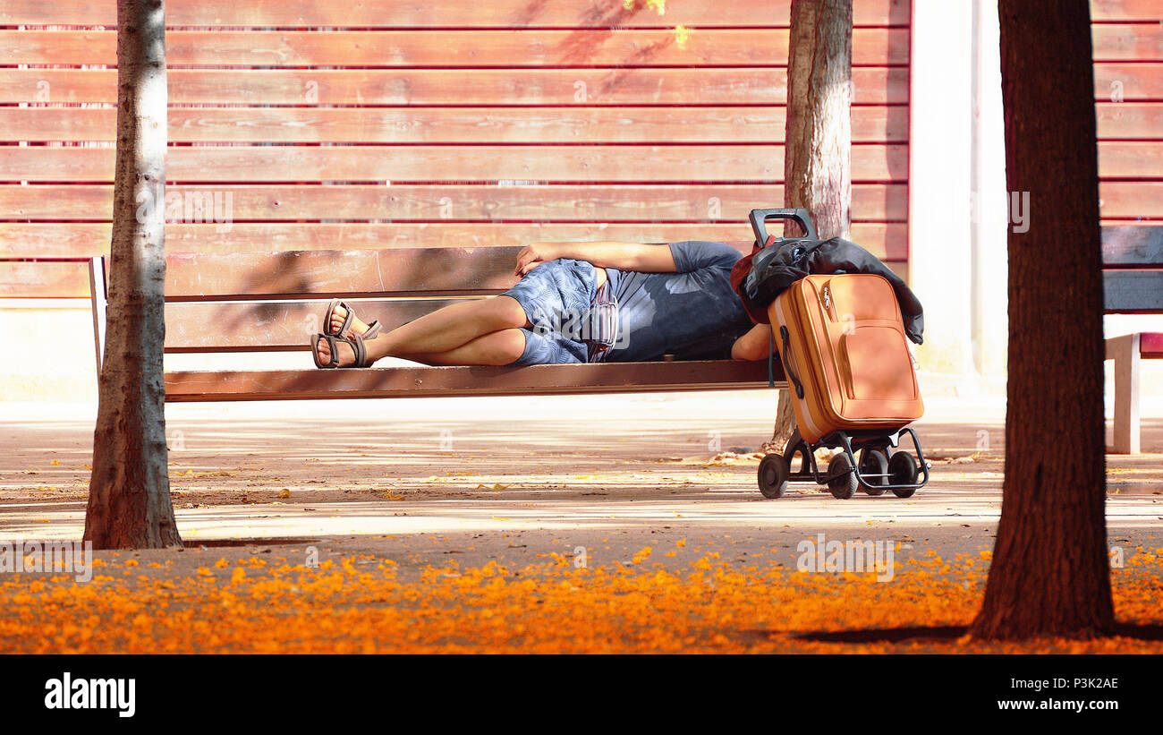 Indigent man sleeping on a bench in a park. Homeless and social problem concept. Empty copy space for Editor's content. - Stock Image