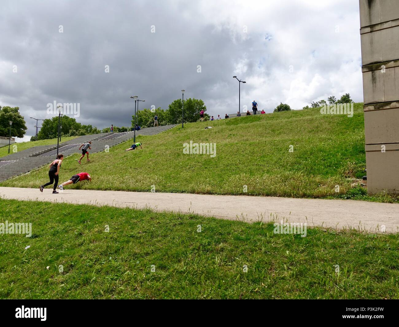 People in a group class working out on a hill in Bercy Park, Paris, France - Stock Image