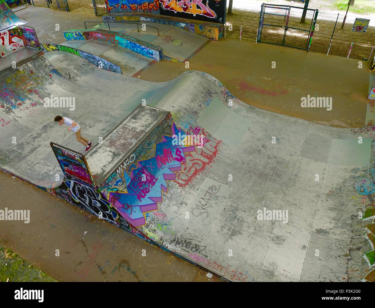 Boy in skatepark decorated with grafitti at Bercy Park, Paris, France Stock Photo
