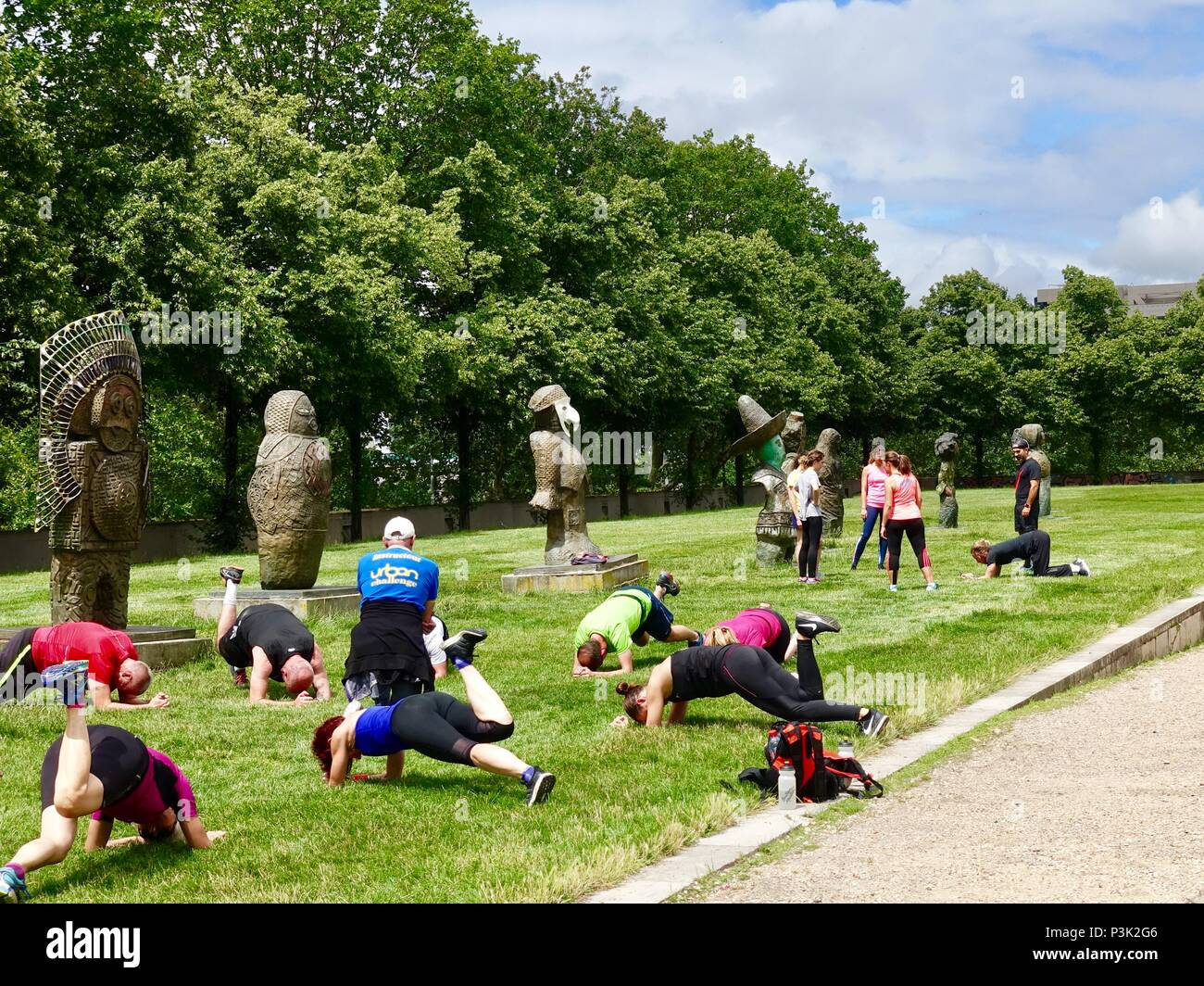Fitness class works out among statues of the 'Children of the World,' any artist Rachid Khimoune, Bercy Park, Paris, France - Stock Image