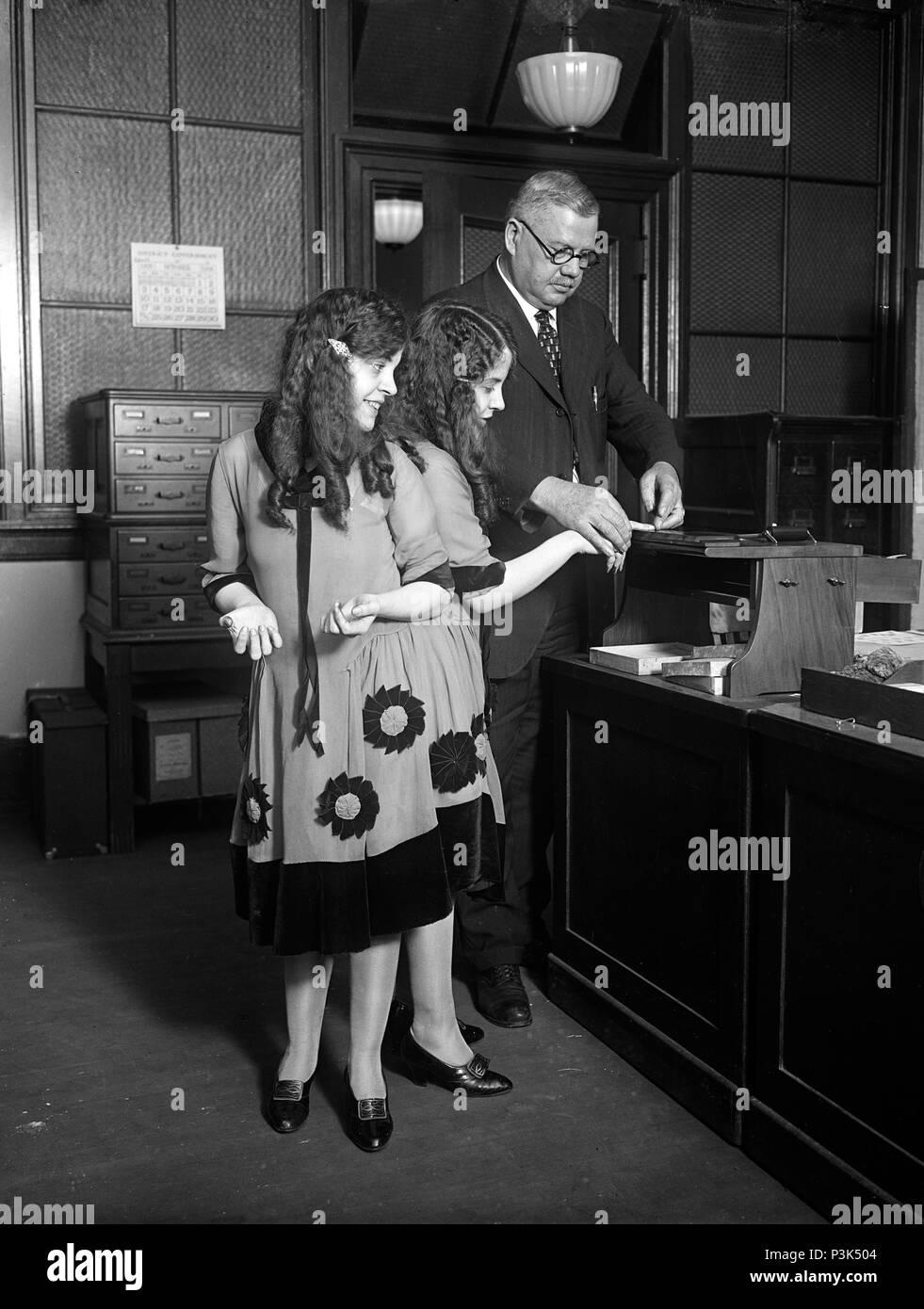 Daisy and Violet Hilton get fingerprinted. Fred Sandberg, District police fingerprint expert, tells Daisy and Violet Hilton, 'Siamese Twins,' apart by their fingerprints - Stock Image