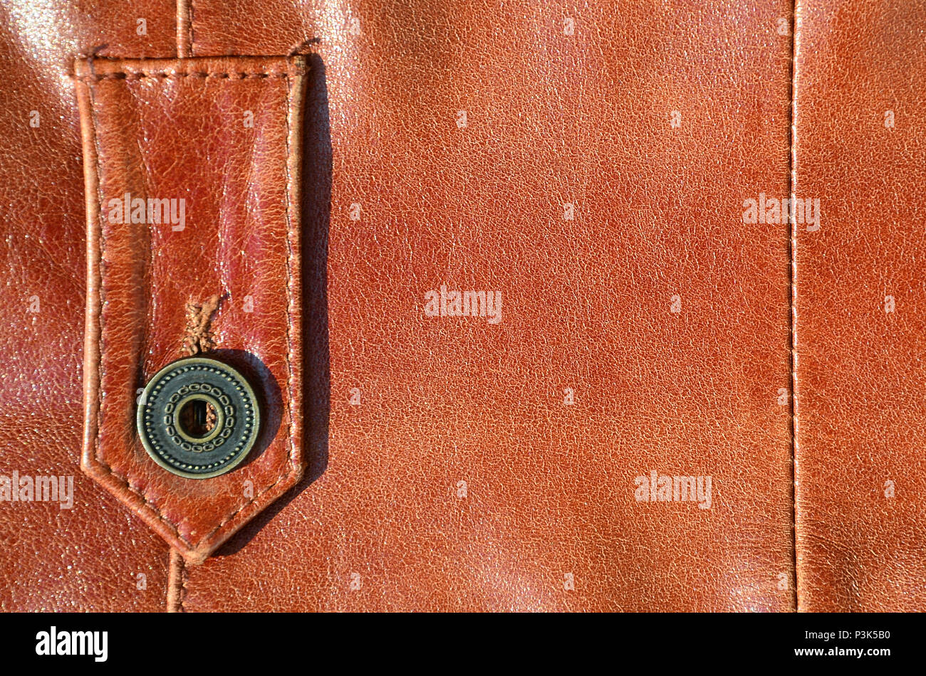 Brown leather texture. Useful as background for any design work. Macro photo of a button on outer clothing made of genuine leather - Stock Image