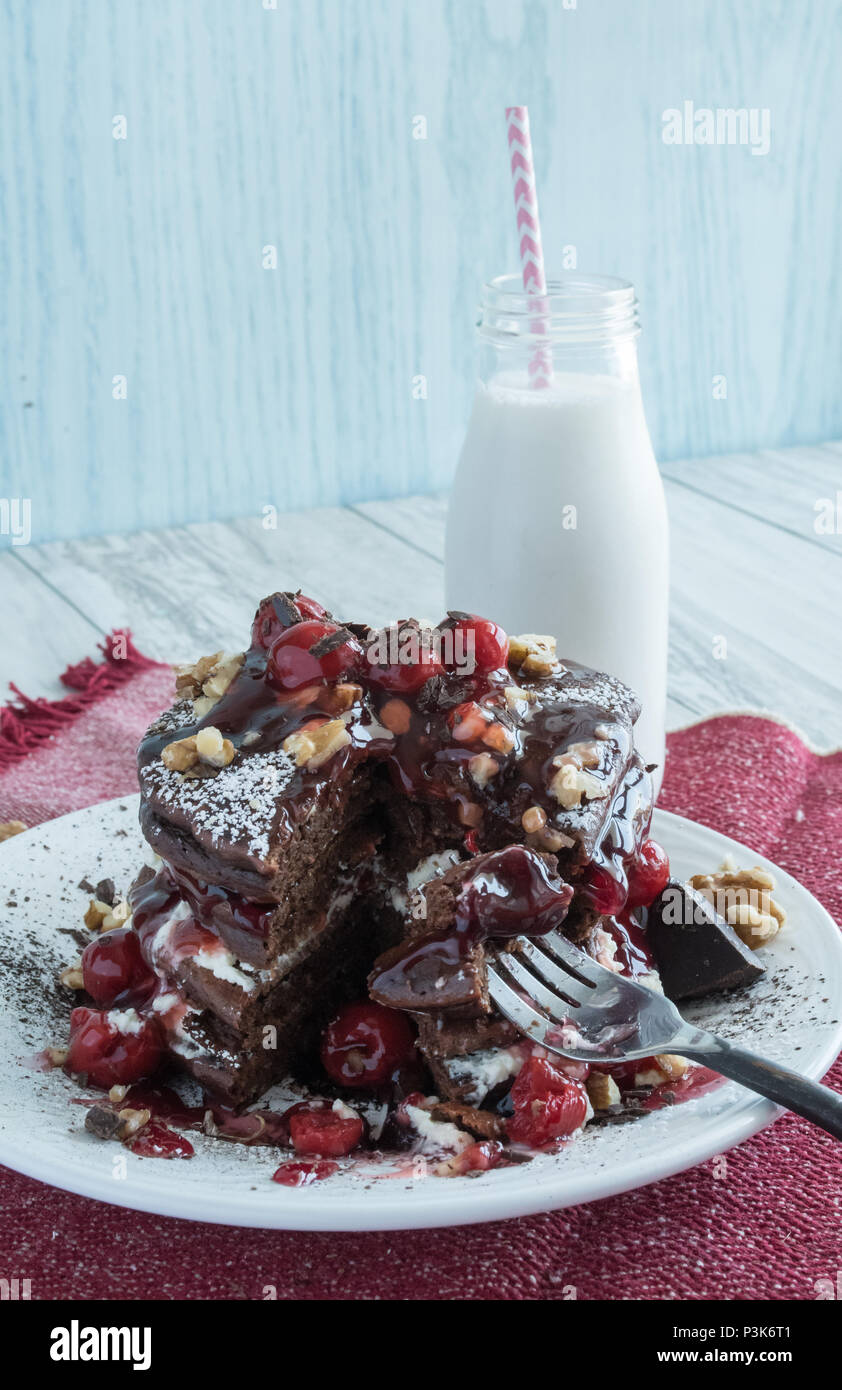 Delicious Chocolate Pancakes - Gourmet Dessert for Breakfast? Closeup of stacked pancakes garnished with cherries, cream, and walnuts. Various angles - Stock Image