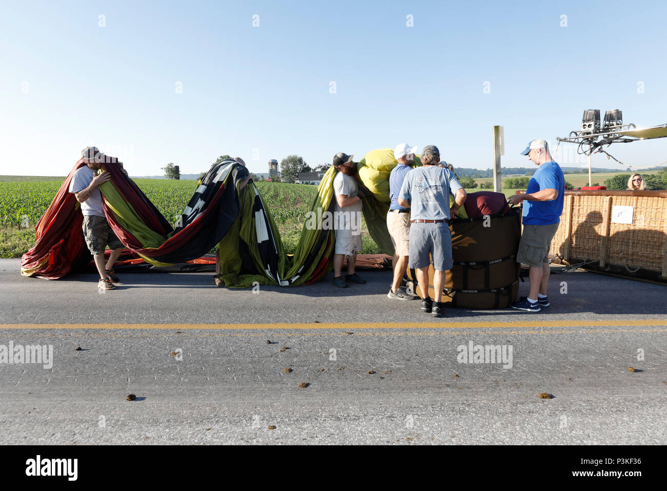 Passengers helping with folding hot air balloon after flight, Lancaster County, Pennsylvania, USA Stock Photo