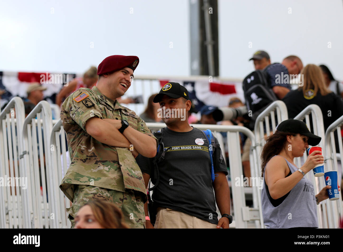 Spc. Nicholas Redding with the 3rd Military Information Support Battalion interacts with a spectator during the social media takeover Redding volunteered to do with Major League Baseball as the Atlanta Braves and Miami Marlins faceoff at Fort Bragg Field, Fort Bragg, N.C. on Sunday, July 3, 2016. Fort Bragg, MLB and the MLB Players Association teamed up to put on the historic regular season game between the Braves and Marlins at Fort Bragg. (US Army photo by Staff Sgt. Jason Duhr) - Stock Image