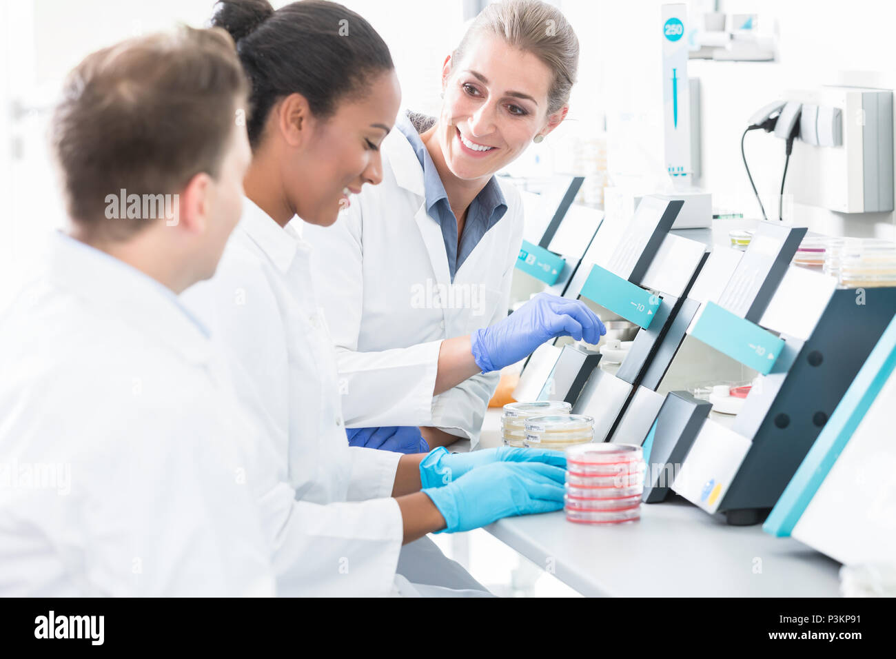Group of researchers using scientific technology for test of samples - Stock Image