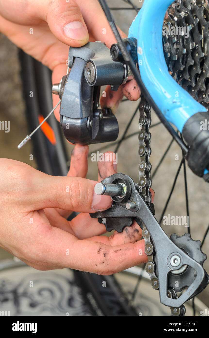 Broken Bicycle Rear Derailleur. Hands Hold the Parts of the Rear Derailleur, Which Fell Apart in Half. Trying to Repair a Breakdown. - Stock Image
