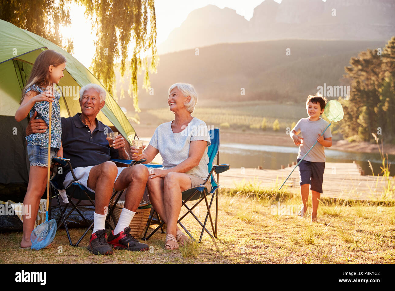 Grandchildren With Grandparents On Camping Holiday By Lake - Stock Image