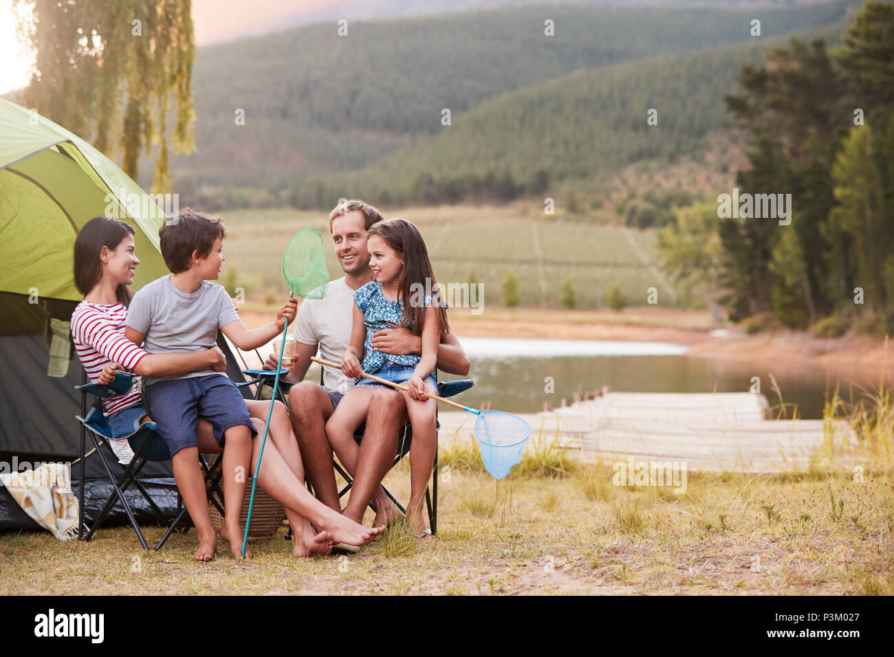 Family Enjoying Camping Vacation By Lake Together - Stock Image