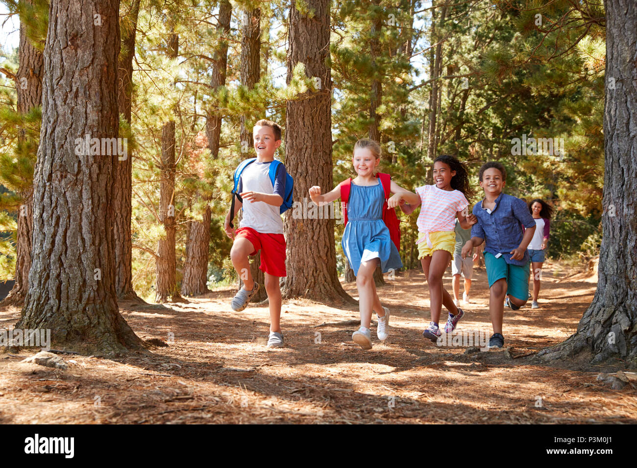 Children Running Ahead Of Parents On Family Hiking Adventure - Stock Image